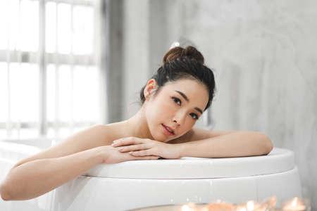 Schöne junge Asiatin genießt es, ein Bad mit Schaumschaum in der Badewanne im Badezimmer zu nehmen? Standard-Bild