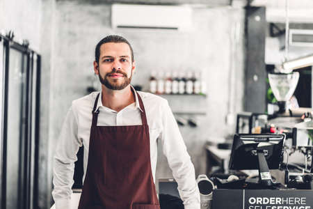 Portrait of handsome bearded barista man small business owner smiling behind the counter bar in a cafe