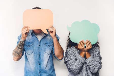 Deux amis tenant une icône de bulle de dialogue ensemble