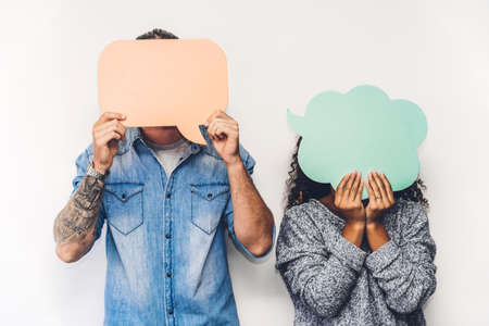 Two friends holding a speech bubble icon together