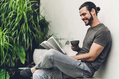 Handsome bearded hipster man relaxing holding and reading book with coffee while sitting on chair in cafe Stock Photo