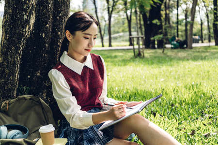 Asia woman students relax reading notebooks sitting under a tree on grass in park.Education concept