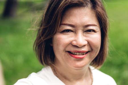Porträt von glücklichen älteren erwachsenen älteren asiatischen Frauen, die die Kamera im Park lächeln und betrachten