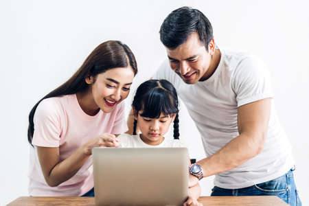 Happy family father and mother with daughter sitting and looking at laptop computer together in the living room at home
