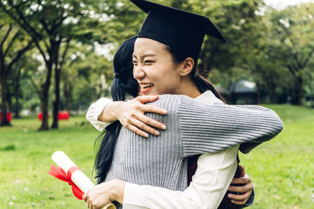 Successful of student young woman and bachelor gowns with diplomas graduate hugging her friend at university.Celebrating graduation and education concept Stok Fotoğraf