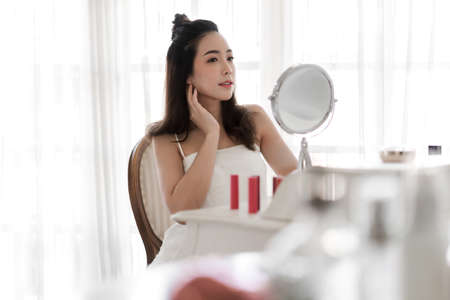 Smiling young beautiful asian woman fresh healthy skin looking on mirror with makeup cosmetics set at home.facial beauty and cosmetic concept Stok Fotoğraf