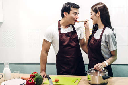 Happy couple cooking and preparing meal together in the kitchen Stok Fotoğraf