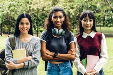 Group of smiling international students or teenagers standing with book in park at university.Education and friendship Concept
