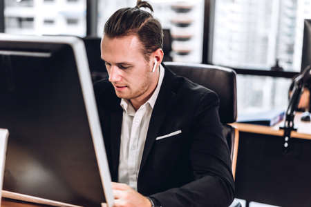 Confident young handsome businessman in black elegant suit sitting and working with computer in modern officeBusiness and startup idea concept