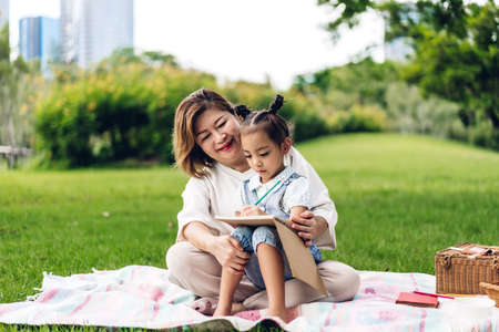Portrait of happy grandmother and little cute girl enjoy relax reading a book together in summer park.Family and togetherness