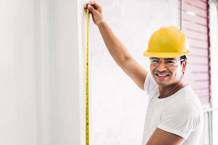 Young construction engineer in a yellow helmet working and  making measurements on the wall at building home site Stok Fotoğraf