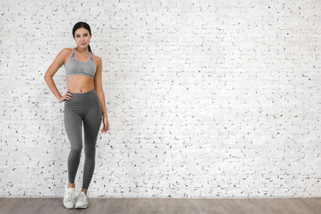 Sport woman in sportswear relax stand after workout against copy space for adding text with white wall background.Diet concept.Fitness and healthy lifestyle Stok Fotoğraf