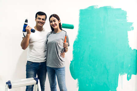 Happy couple using a paint roller and painting walls in their new home Stok Fotoğraf