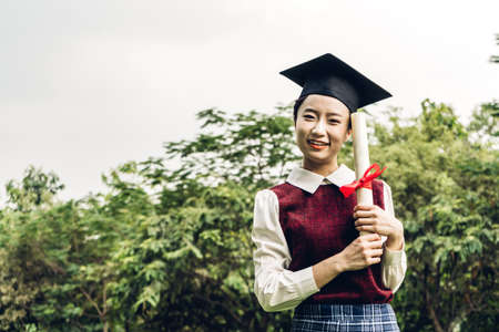 Successful of student young woman and bachelor gowns with diplomas graduate at park in the university.Celebrating graduation and education concept