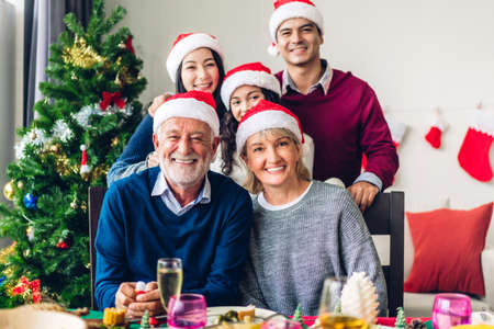 Portrait of happy big family celebrating santa hats having fun and lunch together look at camera and enjoying spending time together in christmas time at home Zdjęcie Seryjne