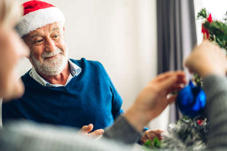 Romantic sweet senior couple relaxing  decorating christmas tree and smiling while celebrating new year eve and enjoying spending time together in christmas time at home