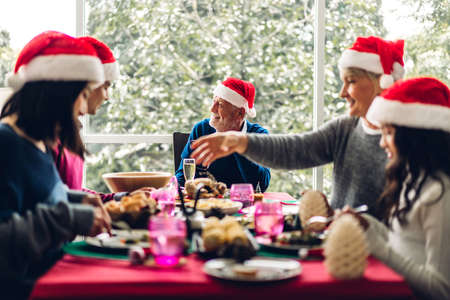 Portrait of happy big family celebrating santa hats having fun and lunch together enjoying spending time together in christmas time at home Zdjęcie Seryjne