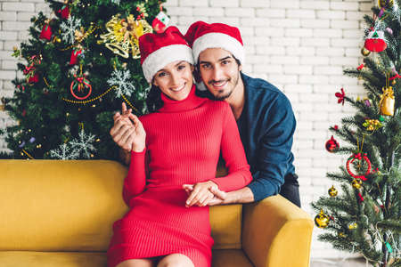 Romantic sweet couple in santa hats having fun decorating christmas tree and smiling while celebrating new year eve and enjoying spending time together in christmas time at home
