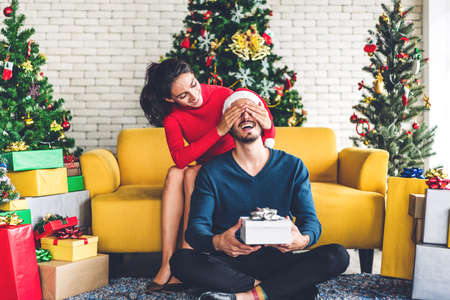 Romantic sweet couple in santa hats having fun decorating christmas tree and smiling while celebrating new year eve and enjoying spending time together.man giving gift box surprise to woman in christmas time at home