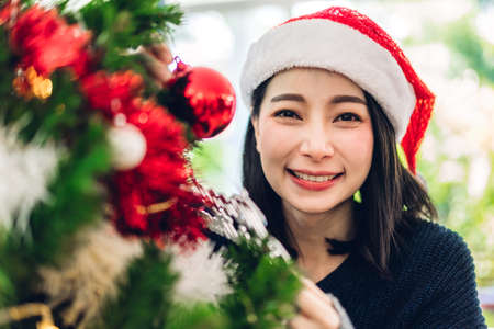 Asia woman in santa hats having fun decorating christmas tree and smiling while celebrating new year eve and enjoying spending time together in christmas time at home