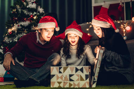 Portrait of happy family father and mother with daughter in santa hats having fun opening magic christmas gift box and enjoying spending time together in christmas time at home Zdjęcie Seryjne