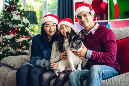 Portrait of happy family father and mother with daughter in santa hats having fun look at camera and enjoying spending time together in christmas time at home
