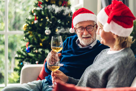 Senior couple relax talking and drinking wine glasses together on sofa in living room at home.Retirement couple concept Zdjęcie Seryjne