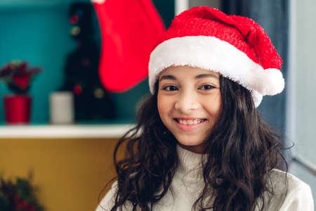 Cute girl in santa hats smiling and look at camera while celebrating new year eve and enjoying spending time together in christmas time at home