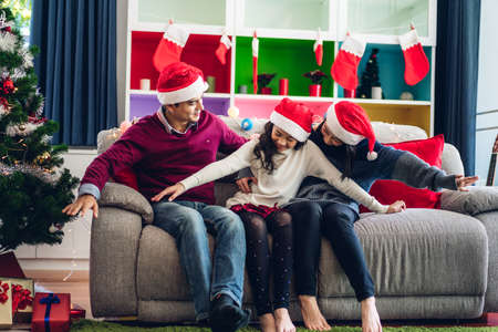 Portrait of happy asian family father and mother with daughter in santa hats having fun look at camera and enjoying spending time together in christmas time at home