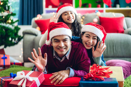 Portrait of happy family father and mother with daughter in santa hats having fun smiling at camera waving and saying hello to you and enjoying spending time together in christmas time at home
