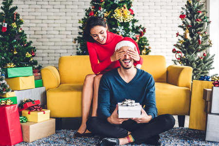 Romantic sweet couple in santa hats having fun decorating christmas tree and smiling while celebrating new year eve and enjoying spending time together.man giving gift box surprise to woman