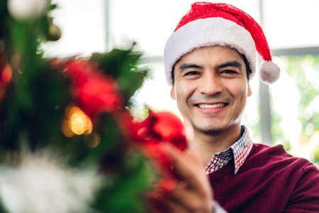 Asia man in santa hats having fun decorating christmas tree and smiling while celebrating new year eve and enjoying spending time together in christmas time at home