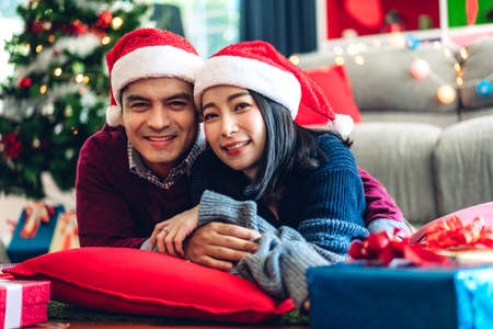 Romantic sweet couple in santa hats having fun and smiling while celebrating new year eve and enjoying spending time together in christmas time at home Zdjęcie Seryjne