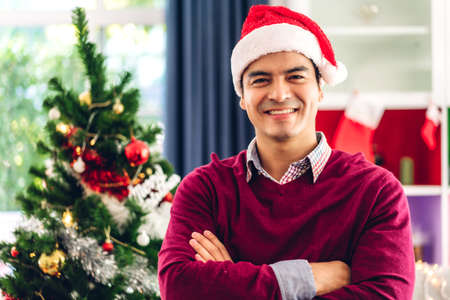Man in santa hats smiling and look at camera while celebrating new year eve and enjoying spending time together in christmas time at home
