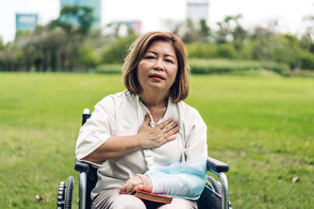 Asian senior adult elderly women sit on wheelchair with chest pain suffering from heart attack in the park.Healthcare and medical concept