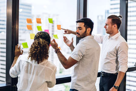 Group of casual business people planning and brainstorm writing over the project with stickers note on glass window at modern office.Teamwork concept