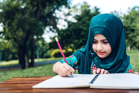 Portrait of happy little muslim girls child with hijab dress smiling and enjoy relax reading and write a book in summer park.Education concept