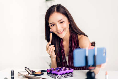 Woman blogger in front of camera recording vlog herself talking about with makeup cosmetics for internet social networks at home