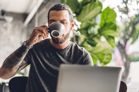 Handsome bearded hipster man use and looking at laptop computer with coffee at table in cafe.Communication and technology concept 免版税图像