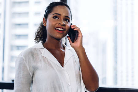 Smiling beautiful professional business african american black woman working and using smartphone standing in office