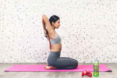 Sport woman sitting relax on pink mat and do fitness exercise with water bottle at home.Diet concept.Fitness and healthy lifestyle 免版税图像