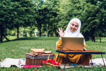 Portrait of happy arabic muslim woman with hijab dress smiling using and talking on the smartphone in summer park