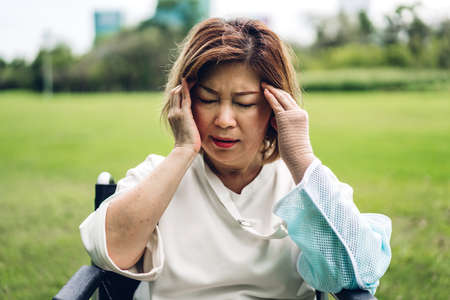 Senior adult elderly asia women serious depressed and feeling headache, thinking of problems at park 免版税图像