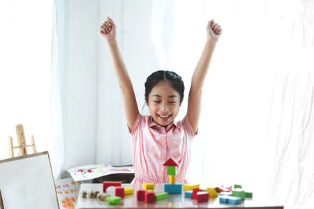 Little cute girl enjoy while playing wooden blocks toys on table at home