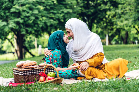 Portrait of happy muslim mother and little muslim girls child  with hijab dress smiling and enjoy relax in summer park.Education concept 免版税图像