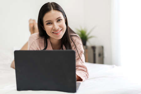 Young woman relaxing using laptop computer on a cold winter day in the bedroom.woman checking social apps and working.Communication and technology concept