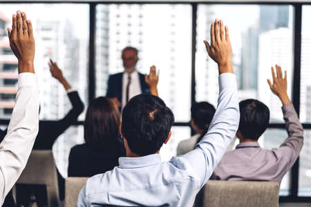 Businessman standing in front of group of people in consulting meeting conference seminar and showing hand to answer question at hall or seminar room.presentation and coaching concept 免版税图像