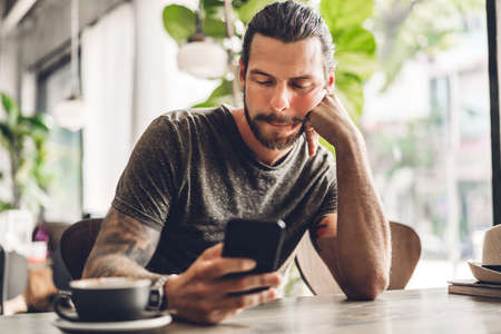 Handsome bearded hipster man use smartphone with coffee at table in cafe.Communication and technology concept Stok Fotoğraf