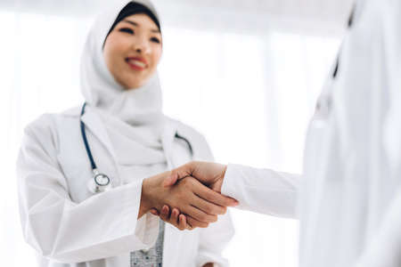 Success of handshake two muslim asian woman doctor in hospital.healthcare and medicine