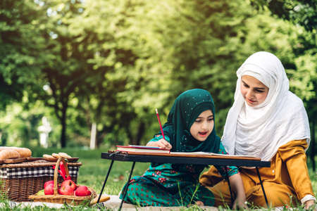 Portrait of happy muslim mother and little muslim girls child learning together with hijab dress smiling and enjoy relax reading and write a book in summer park.Education concept